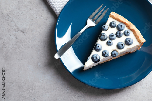 Piece of tasty blueberry cake and space for text on gray table, top view