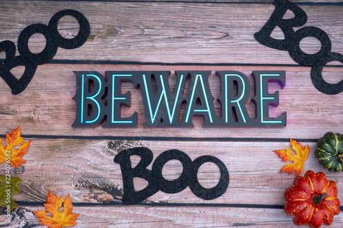 Fototapeta Beware boo Halloween background on wood backdrop with pumpkins and maple leaves