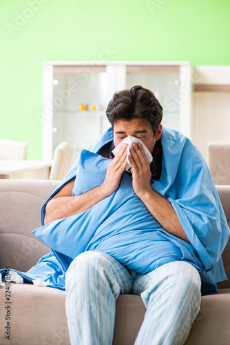 Fotografia  Sick young man suffering from flu at home