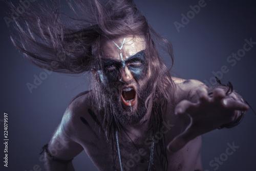 Fotografie, Obraz  Dark tribal shaman or warlock summoning spirits using a deer skull and his ritua