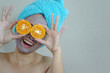 Happy woman with a clay mask with biting slice of orange.