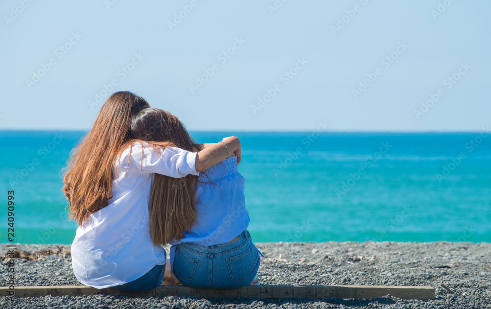 Fototapety, obrazy: Lovely teenager sister sitting and relax at the black sand beach in Napier. Summer holiday in New Zealand.
