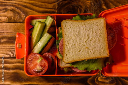 Foto op Aluminium Assortiment Lunch box with sandwich, cucumbers and tomatoes on wooden table. Top view