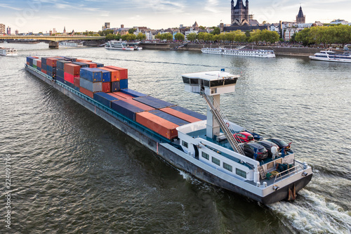 A large barge loaded with shipping containers floating on the river Rhine in Cologne.