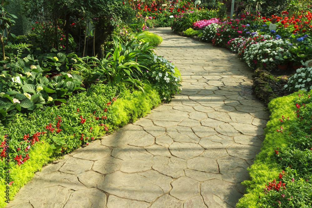 Fototapeta Stone walkway in flower garden.