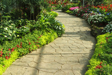 Stone Walkway In Flower Garden.