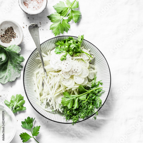 Fototapeta Daikon and kohlrabi cabbage slaw salad on light background, top view obraz