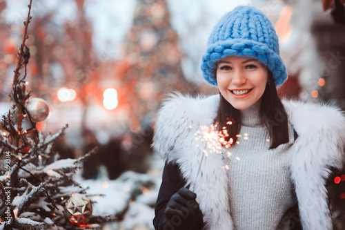 Photo christmas portrait of happy woman with burning firelight walking outdoor in snow