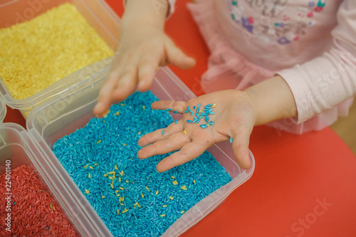 Fototapeta Child hands playing with colored rice in the sensory box. Baby's sensory educational kit obraz