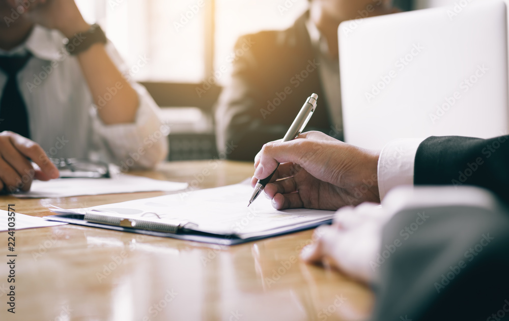 Fototapeta Boardroom with human resource business people writing paper negotiating a contract.