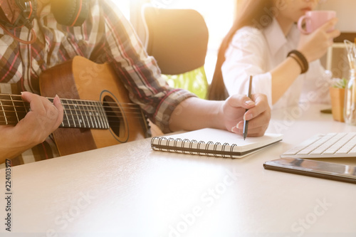 Photo  musician songwriter working with guitar and notepad paper on workplace with cropped shot