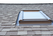 Grey Asphalt Shingles House Roofing Construction With Attic Roof Window Skylights Waterproofing Closeup View.