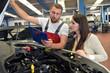 Kundendienst in der KFZ Werkstatt: Automechaniker berät Kundin wegen Reparaturauftrag // Customer service in the car workshop: Car mechanic advises customer on repair order