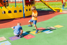 Two Boys Playing Hopscotch In The Summer Outdoors