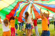 canvas print picture Joyous classmates jumping under colorful parachute in the summer outdoors