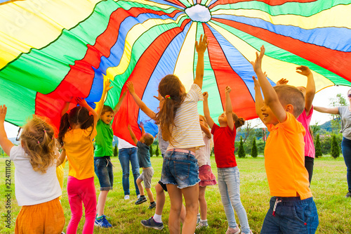 Fototapeta Joyous classmates jumping under colorful parachute in the summer outdoors obraz