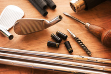 Custom Golf Clubs Or Club Modifications. Golf Club Components On A Work Desk Or Work Bench. Grips, Shaft, Ferrules And, Iron Head. Focus Is On Black Ferrule Parts. Shallow Depth Of Field.