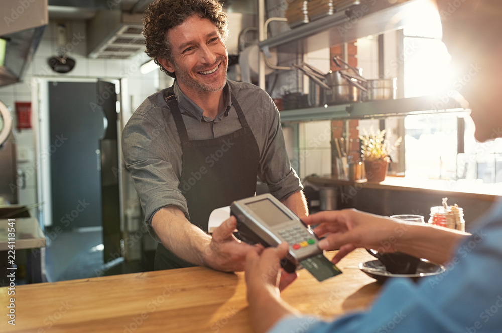 Fototapeta Waiter accepting payment by card
