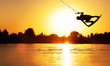 canvas print picture - Wake Board a man does a trick at sunset on the Board on the water splashes