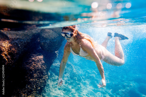 Wall Murals Green coral Young woman snorkeling underwater in the clear tropical water