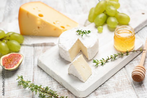 Cheese, grapes, honey and herbs on white board. Selective focus. Tasty cheese plate