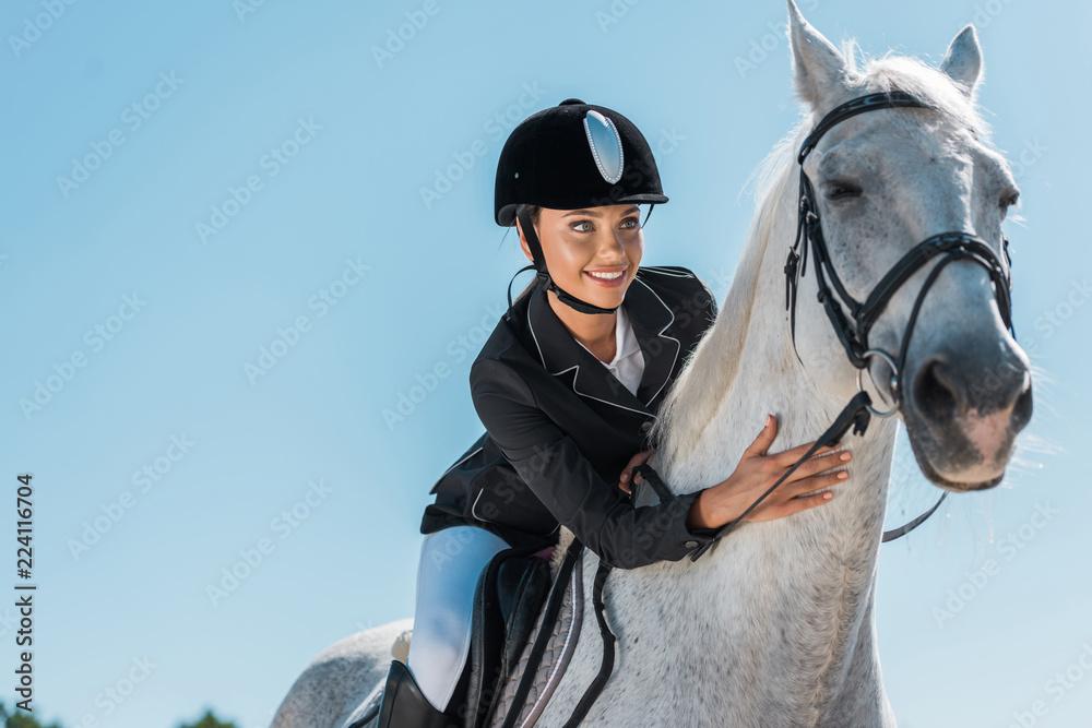 Fototapeta attractive female equestrian riding beautiful white horse at horse club