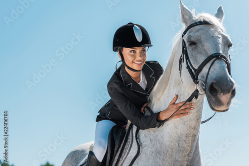 attractive female equestrian riding beautiful white horse at horse club Fototapeta