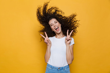 Image of european woman 20s laughing and having fun with shaking hair, isolated over yellow background