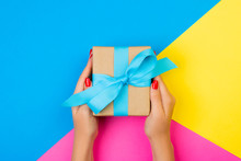 Woman Hands Holding Gift Wrapped And Decorated With Blue Bow On Blue, Pink And Yellow Background With Copy Space
