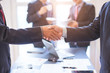 After meeting business people shaking hands with new partner meeting to jointly invest in business together.