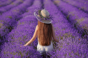 Beautiful healthy long hair. Back view of Young teen girl in hat over lavender field. Happy carefree woman with shiny hairstyle enjoying sunset. Outdoors portrait. Provence, France.