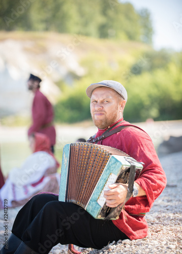 A man in Russian national costume stand on the background of