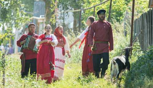 Group of men and women in russian folk costumes in nature singing. Celebration