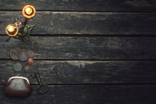 Burning Candle, Wallet, Rusty Key And Old Coins Of Russian Empire Scattered On Wooden Table Background With Copy Space.