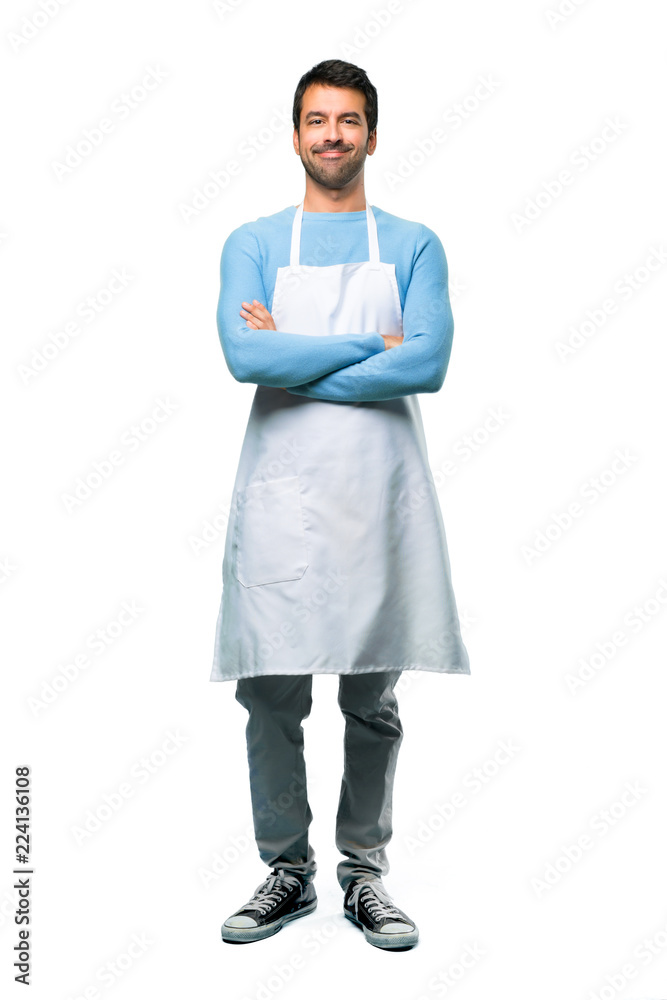 Fototapeta A full-length shot of a Man wearing an apron keeping the arms crossed in frontal position. Confident expression on isolated background