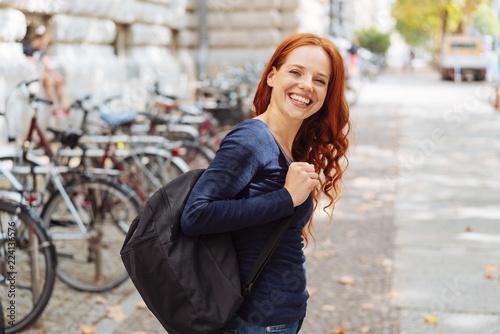 lachende junge frau mit rucksack ist in der stadt unterwegs Canvas Print