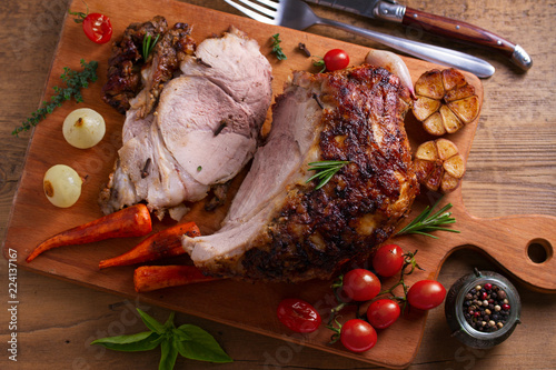 Baked ham with vegetables: carrots, onions, tomatoes, garlic and herbs on chopping board. View from above, top studio shot
