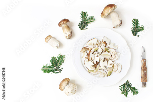 Autumn styled food arrangement. Composition of whole and sliced porcino mushrooms, Boletus edulis on white plate, fir branches and pocket knife. White table background. Fall design, flat lay, top view