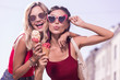 Best friends. Delighted young women standing together while holding ice cream cones