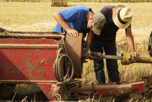 Tractor And Straw Baler In Wheat Field, Two Farmers Checking Equipment.