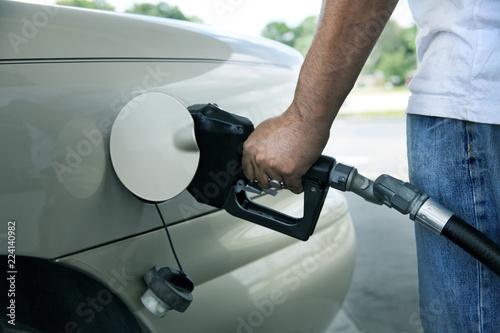 Fotografie, Obraz  close up male hand holding gas pump filling gas tank