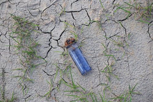 Fotografía  Closeup of clear blue lighter with rusty flint in dry cracked soil