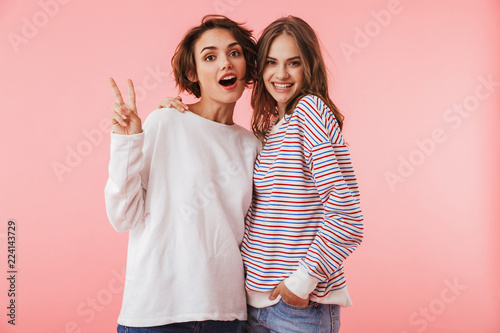 Fototapeta Women friends isolated over pink wall background posing. obraz