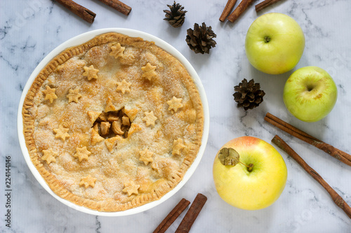 Photo  A traditional American apple pie decorated with stars and sugar, apples and cinnamon on a light background