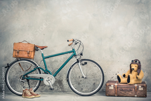 Photo sur Aluminium Velo Retro bicycle with leather mailman's bag, old sneakers and Teddy Bear toy in leather aviator's hat and goggles sitting on aged classic travel suitcase front concrete wall. Vintage style filtered photo