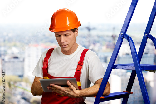 Confident foreman working on digital tablet. Concentrated engineer using pc tablet. People, buildings and maintenance concept.