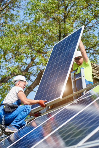 Two technicians standing on metal platform adjusting heavy solar photo voltaic panel on bright sunny day Wallpaper Mural