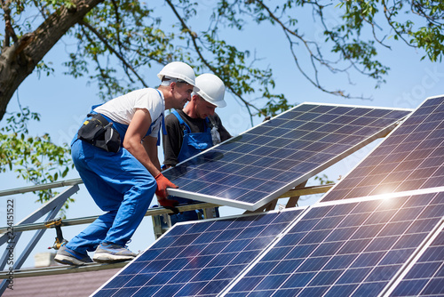 Two young technicians installing heavy solar photo voltaic panel on tall steel platform on green tree background Tablou Canvas