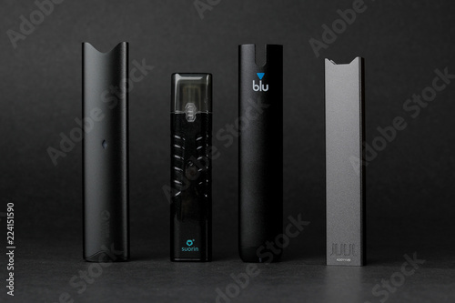 An electronic cigarette device made by JUUL is shown next to other