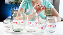 Closeup Image Of Young Woman Putting One Dollar Bill In Glass Jar For Buying New Car